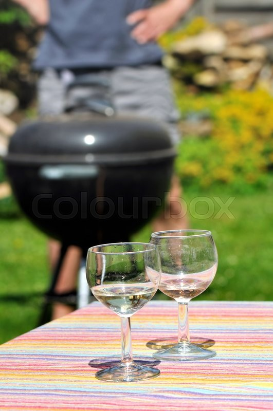 Stock image of 'two wine glasses on table with barbecue background in garden'