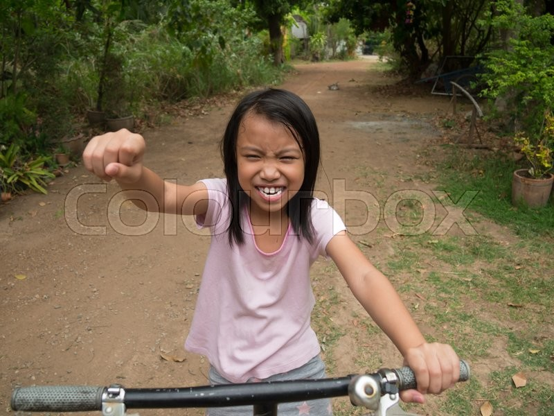 Stock image of 'Happy little asian kid riding bicycle in the park'