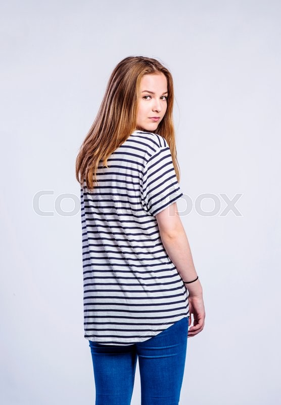 Stock image of 'Teenage girl in jeans and striped t-shirt, young woman, studio shot on gray background, rear view'
