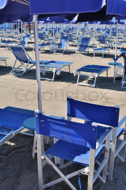 Stock image of 'blue chairs and umbrellas on italian beach'