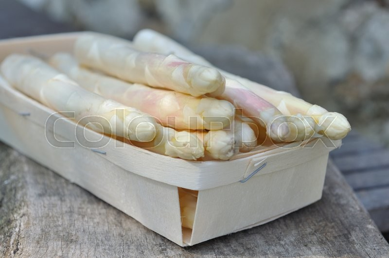 Stock image of 'white asparagus in a little tray on wooden background'