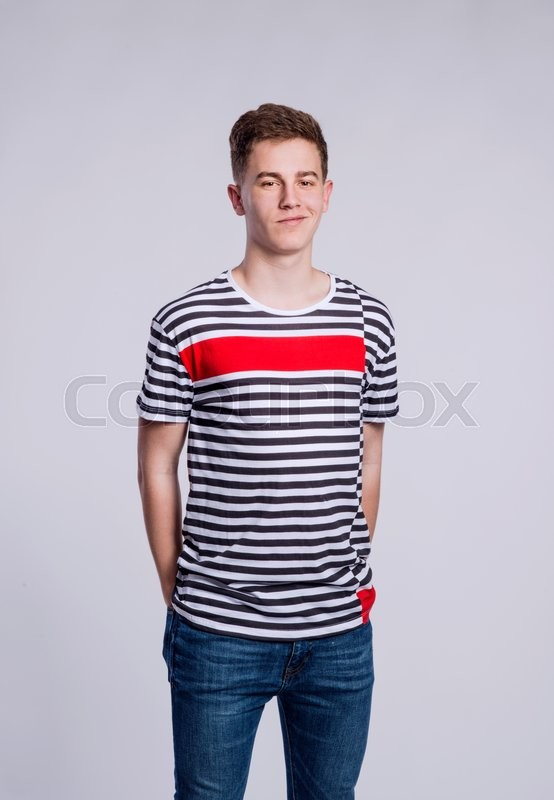 Stock image of 'Teenage boy in jeans and striped t-shirt, young man, studio shot on gray background'