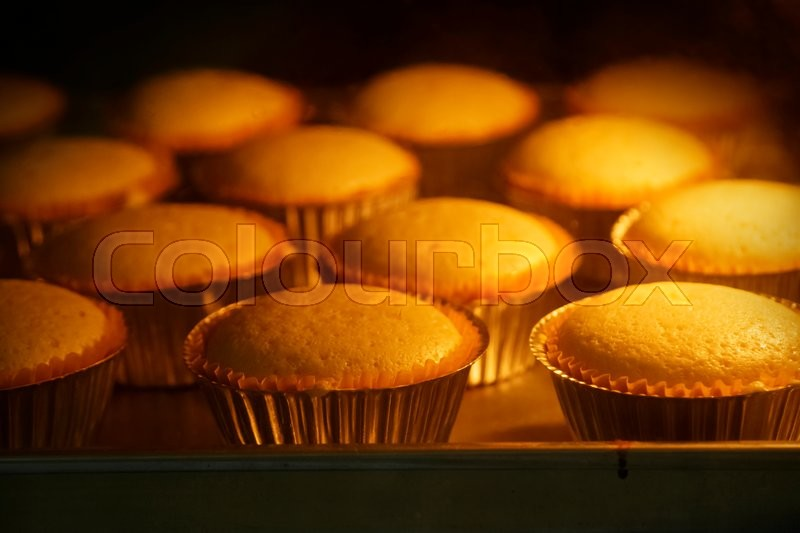 Stock image of 'Cup cakes baking in oven, homemade barkery'