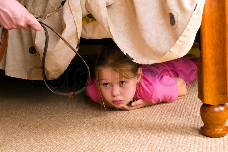 The child hides under a bed. Violence in a family. | Stock Photo ...