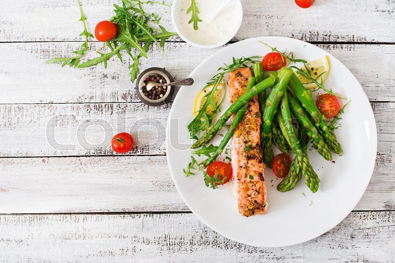 Baked salmon garnished with asparagus and tomatoes with herbs. Top view, stock photo