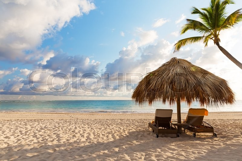 Beach chairs with umbrella and beautiful sand beach in Punta Cana, Dominican Republic, stock photo