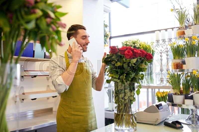 People, sale, retail, business and floristry concept - florist man with red roses calling on smartphone at flower shop counter, stock photo