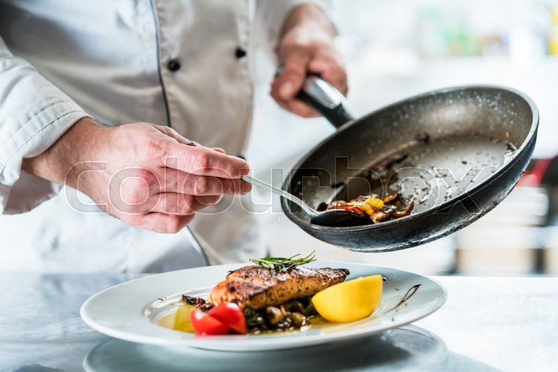 Chef finishing food in his restaurant kitchen, stock photo