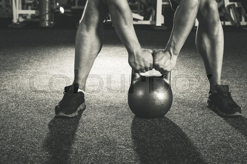 Crossfit kettlebell training in gym, stock photo