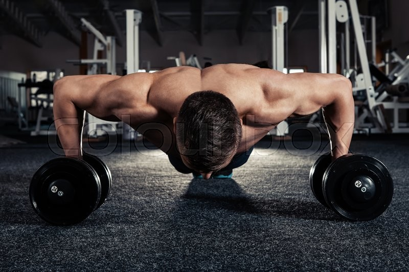 Handsome muscular man doing pushup exercise with dumbbell in a crossfit workout, stock photo
