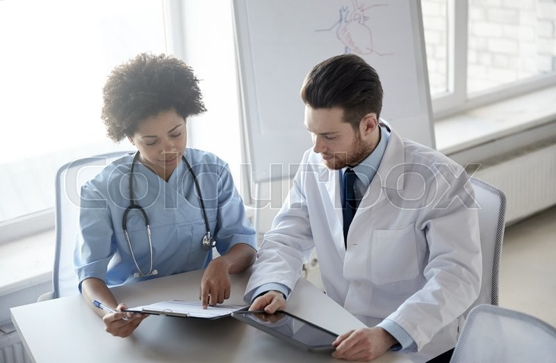 Health care, people, technology and medicine concept - doctor and nurse with tablet pc computer and clipboard meeting and discussing something at hospital, stock photo