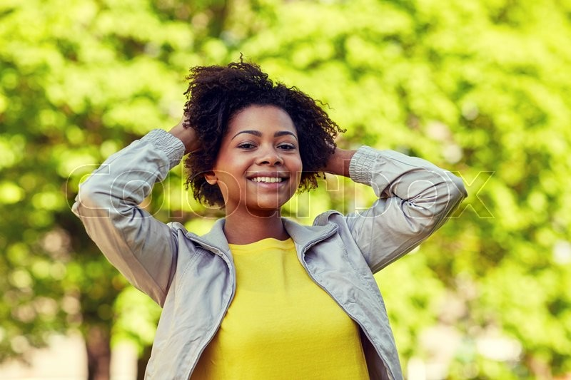 People, race, ethnicity and portrait concept - happy african american young woman in summer park, stock photo