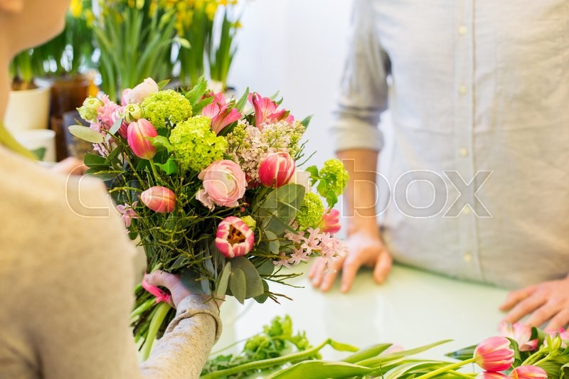 People, shopping, sale, floristry and consumerism concept - close up of florist woman making bouquet for and man or customer at flower shop, stock photo