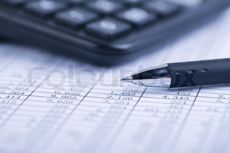 A calculator and a ball pen is on a balance sheet. Concept for sales, profit and cost, stock photo