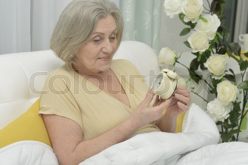 Stock image of 'Senior woman portrait in bed with alarm clock'