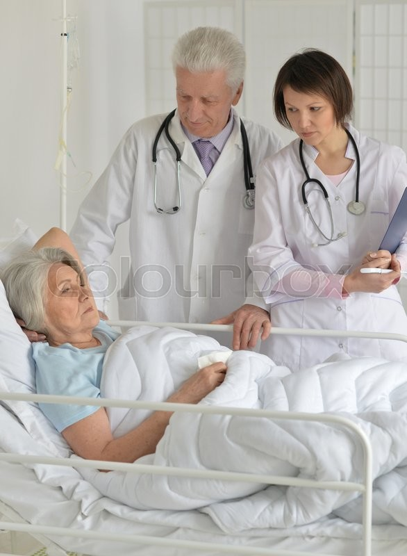 Stock image of 'Senior woman in hospital with caring doctors'