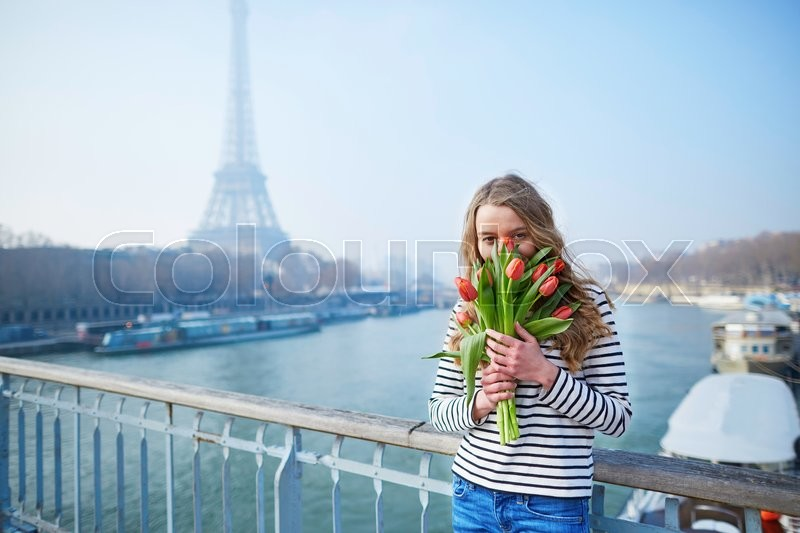Stock image of 'Beautiful young girl with bunch of red tulips near the Eiffel tower'