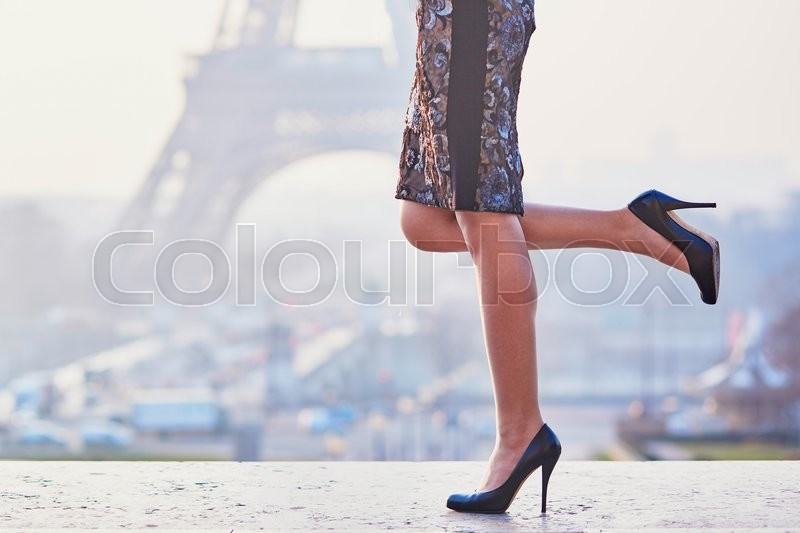 Stock image of 'Woman wearing high heels shoes and walking near the Eiffel tower at early morning in Paris, closeup of legs'