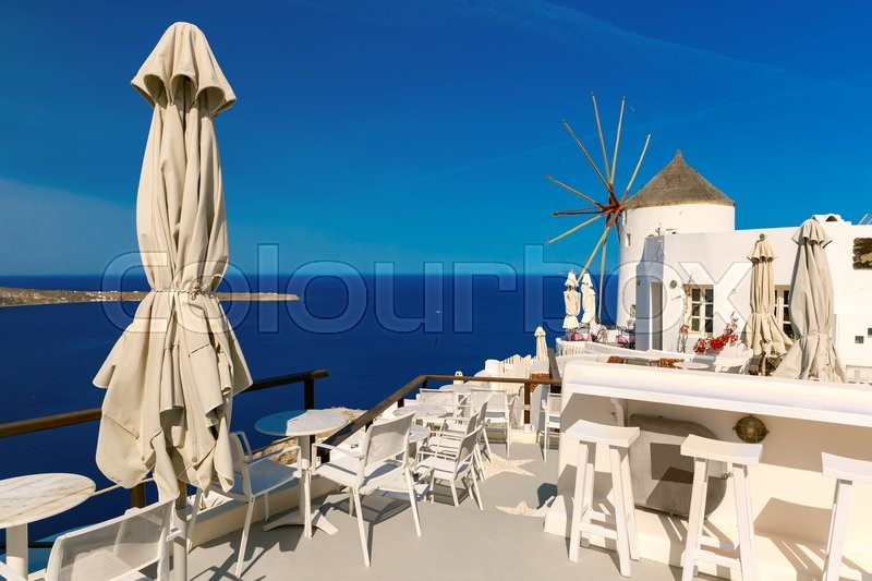 Stock image of 'Picturesque view of windmill, empty restaurant and white houses in Oia or Ia on the island Santorini, Greece'