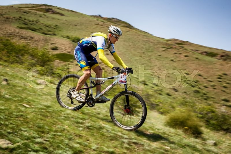Stock image of 'ALMATY, KAZAKHSTAN - MAY 01, 2016: V.Ganja (N11) in action at Adventure mountain bike cross-country competition in mountains