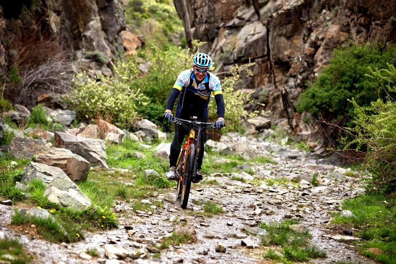 Stock image of 'ALMATY, KAZAKHSTAN - MAY 01, 2016: Unknown rider in action at Adventure mountain bike cross-country competition in mountains