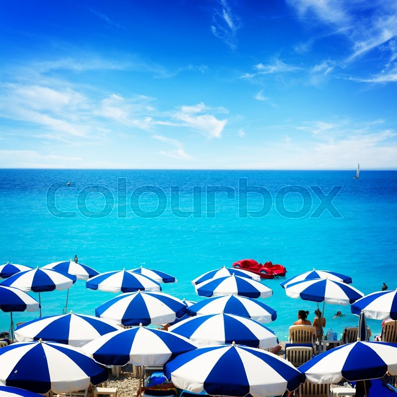 Stock image of 'turquiose water of cote dAzur over striped beach umbrellas, France, retro toned'