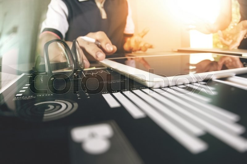 Stock image of 'Business documents on office table with smart phone and digital tablet and graph business with social network diagram and man working in the background'