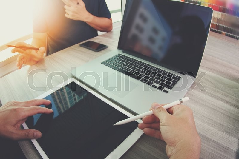 Stock image of 'Two colleagues interior designer discussing data and blank screen digital tablet and computer laptop with smart phone on wooden desk as concept'
