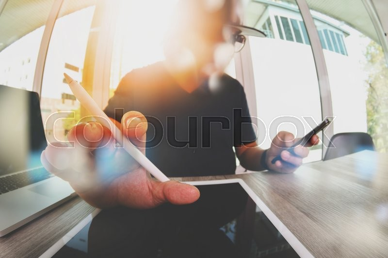 Stock image of 'Website designer working blank screen digital tablet and computer laptop with smart phone on wooden desk as concept'