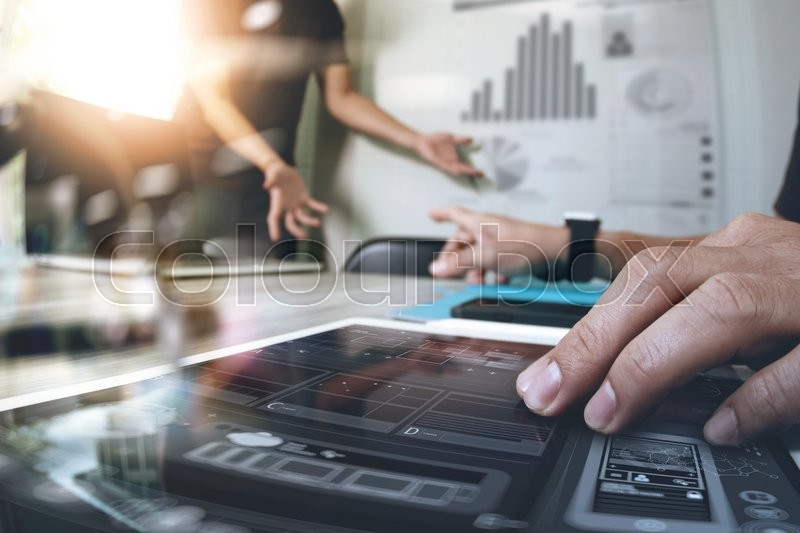 Stock image of 'Two colleague sweb designer discussing data and digital tablet and computer laptop with smart phone and design diagram on wooden desk as concept'