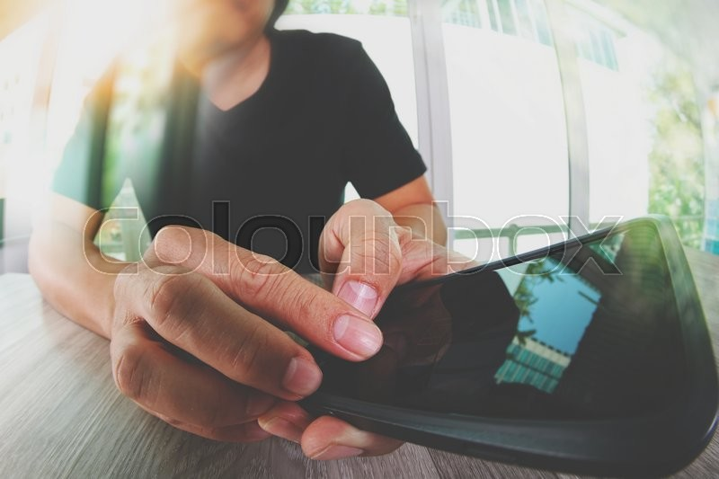 Stock image of 'designer hand working and smart phone on wooden desk in office '