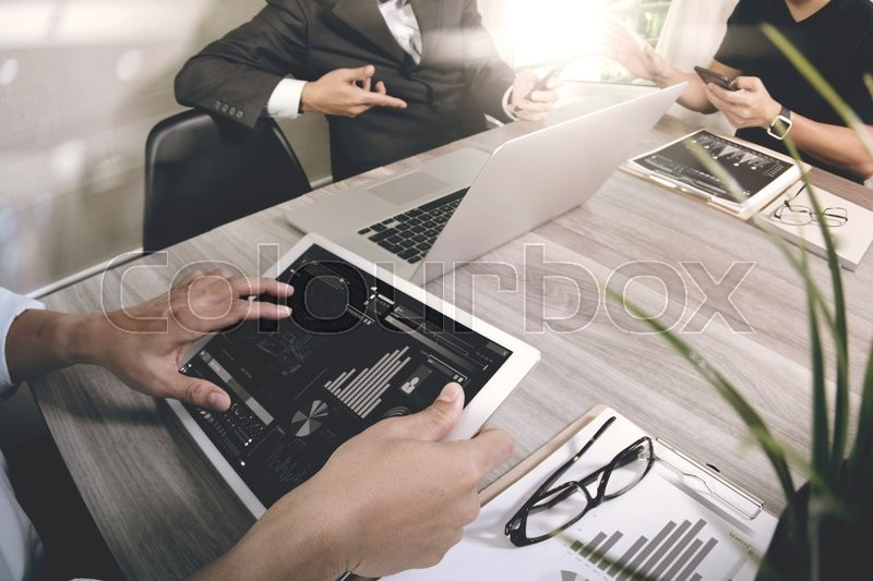 Stock image of 'business documents on office table with smart phone and laptop computer and graph business with social network diagram and three colleagues discussing data in the background  '