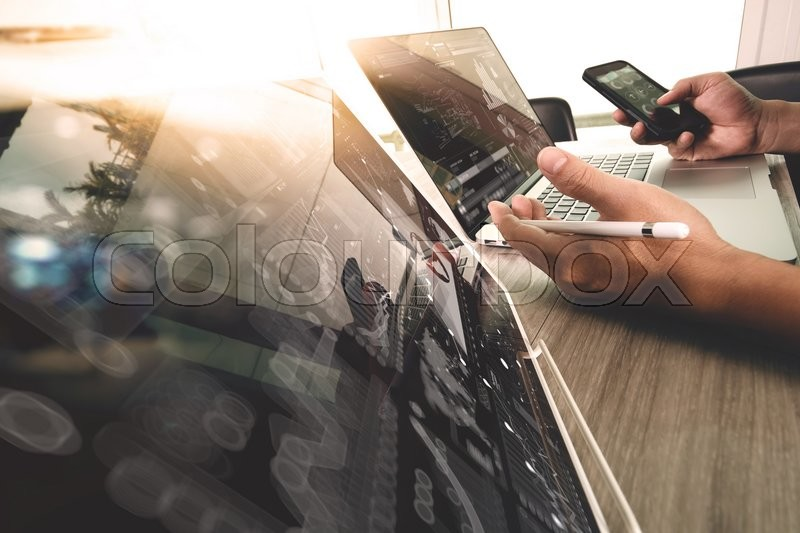 Stock image of 'Designer hand working with digital tablet and laptop computer and book stack and eye glass on wooden desk as concept'