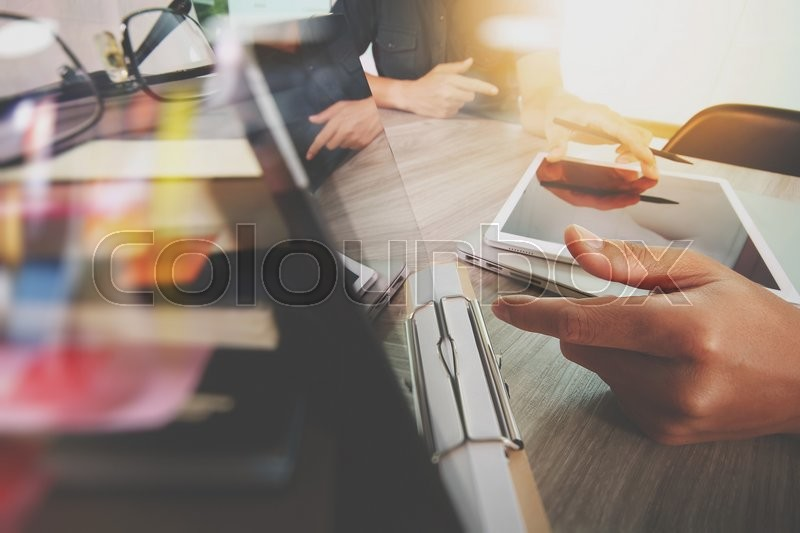 Stock image of 'Businessman making presentation with his colleagues and business tablet digital computer at the office as concept'