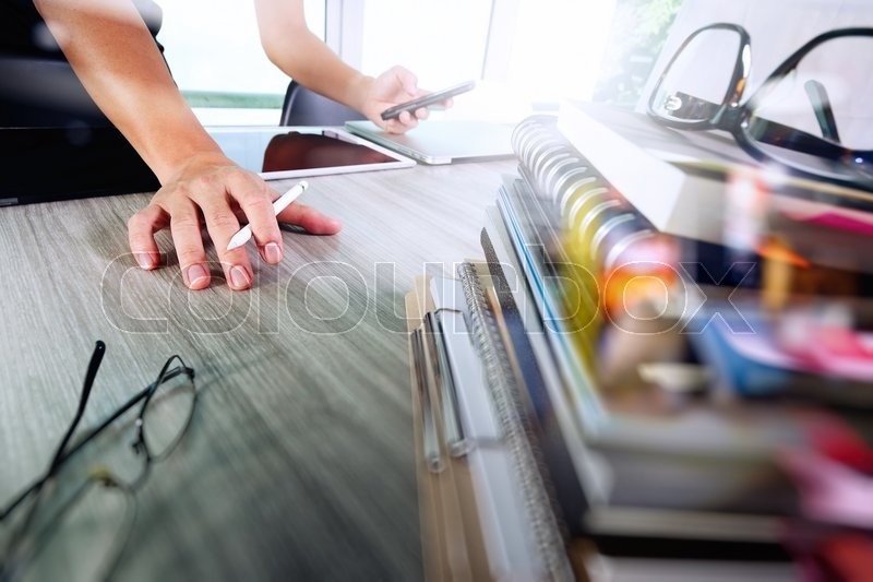 Stock image of 'Designer hand working with digital tablet and laptop and notebook stack and eye glass on wooden desk in office'