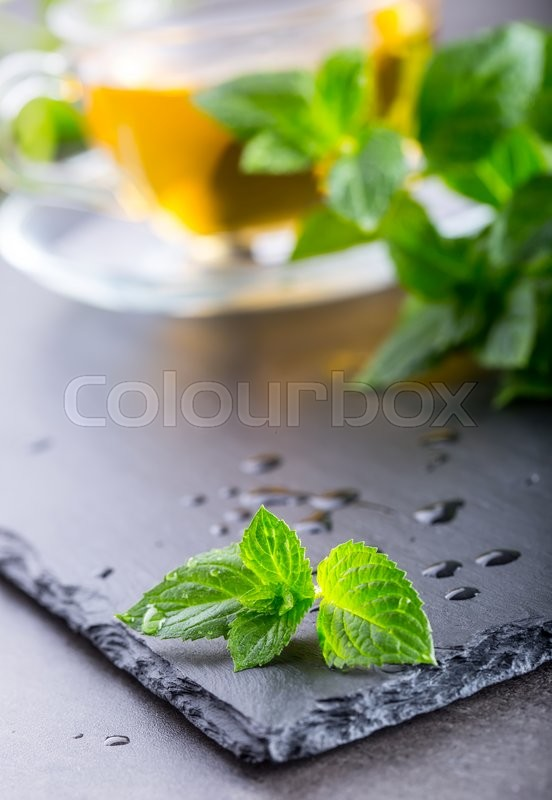 Stock image of 'Mint leaf. Mint leaves. Tea. Mint Tea. Herbal tea. Tea in a glass cup, mint leaves, dried tea, sliced lime. herbs tea and mint leaves on a slate plate in a restaurant or teahouse tea room.'