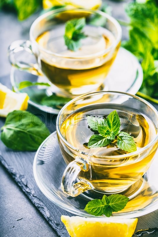 Stock image of 'Tea. Mint Tea. Herbal tea. Mint leaf. Mint leaves. Tea in a glass cup, mint leaves, dried tea, sliced lime. herbs tea and mint leaves on a slate plate in a restaurant or teahouse tea room'