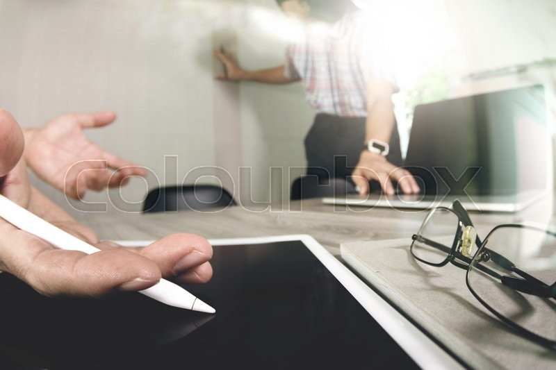 Stock image of 'Two colleagues web designer discussing data and blank screen digital tablet and computer laptop with smart phone on wooden desk as concept'