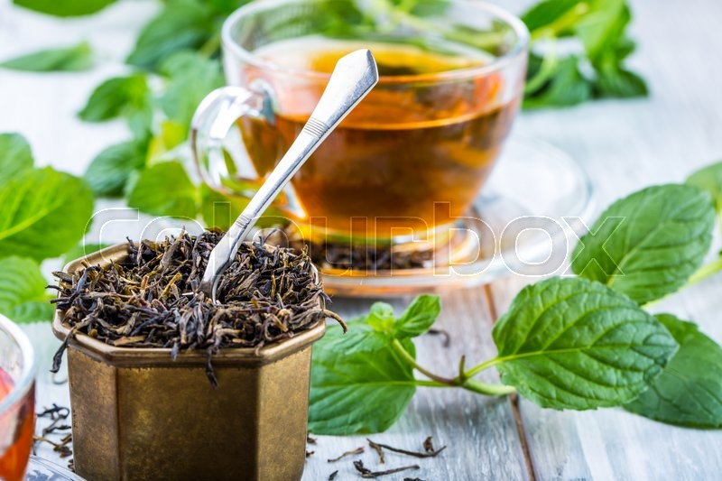 Stock image of 'Tea. Mint Tea. Herbal tea. Mint leaf. Mint leaves. Tea in a glass cup, mint leaves, dried tea, sliced lime. herbs tea and mint leaves on a slate plate in a restaurant or teahouse tea room.'