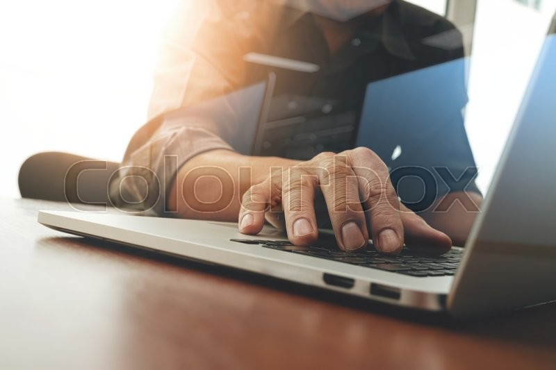 Stock image of 'Business man hand working on laptop computer with business graph information diagram on wooden desk as concept'
