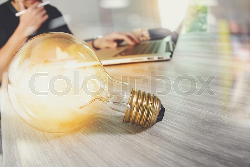 Stock image of 'Light bulb with designer hand working with laptop computer and creative business strategy as concept'