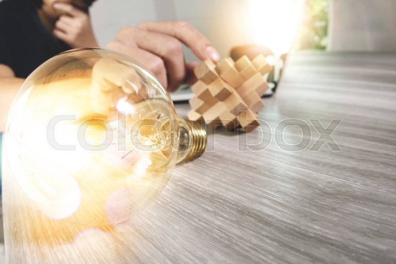 Stock image of 'Creative hand showing wood puzzle and light bulb with laptop computer and tablet computer as design concept'