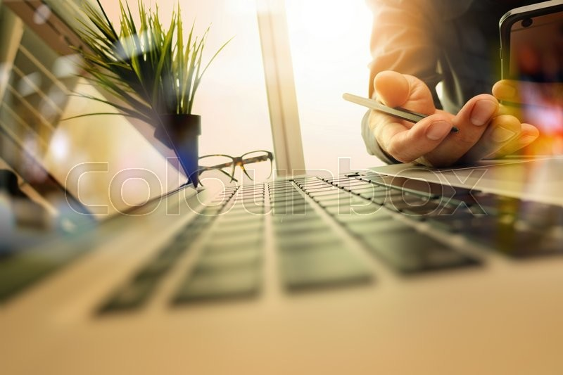 Stock image of 'Designer hand working and smart phone and laptop on wooden desk in office with london city background'
