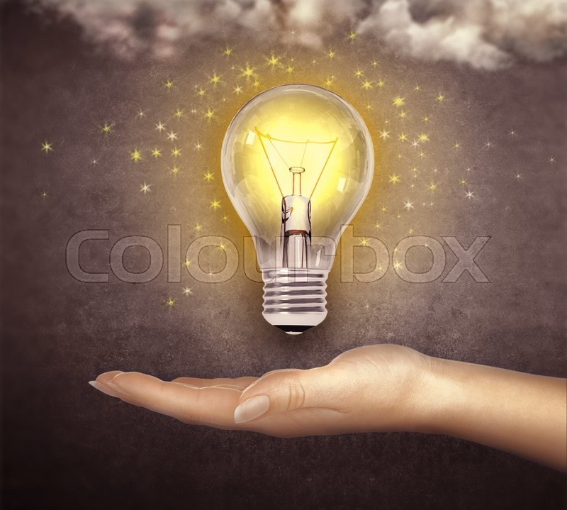 Stock image of 'Glowing bulb above a hand'