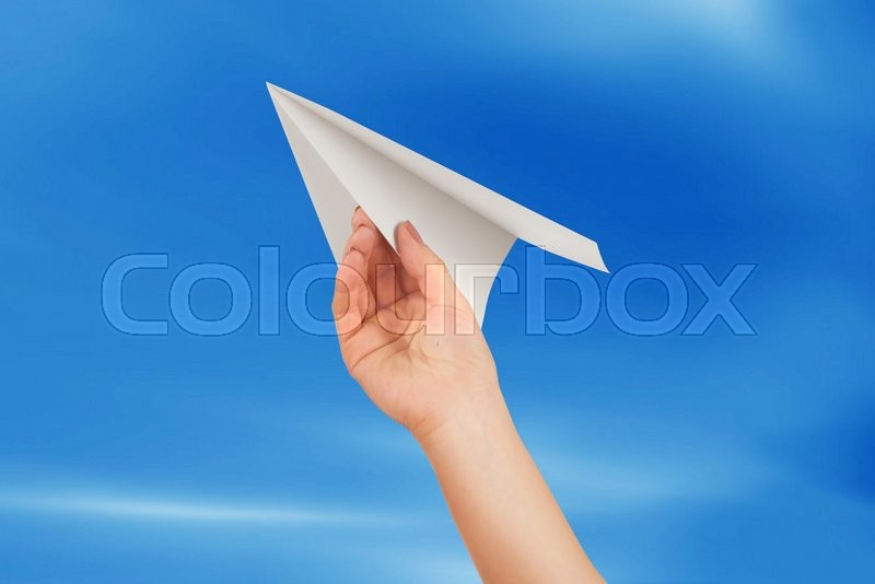 Stock image of 'Businesswoman throwing white paper plane'