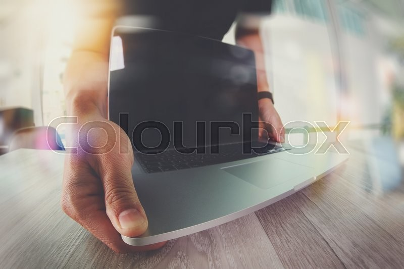 Stock image of 'Designer hand working with blank screen laptop computer on wooden desk as responsive web design concept\\ '