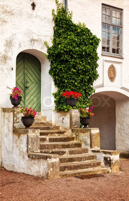 Stock image of 'Image of a rustic courtyard porch by a historic building. '