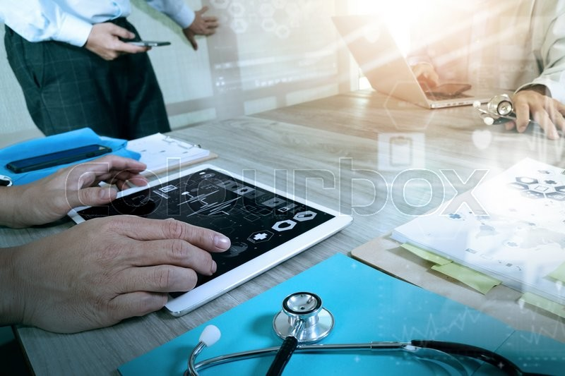 Stock image of 'Medicine doctor hand working with modern computer and digital pro tablet with his team with digital medical diagram on wooden desk as medical concept                               '