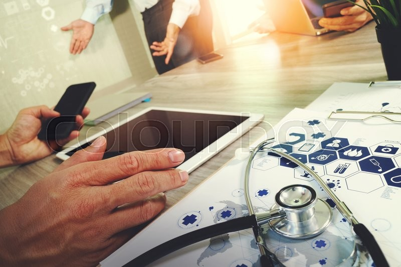 Stock image of 'Medicine doctor hand working with modern computer and digital pro tablet with blank screen with his team on wooden desk as medical concept'