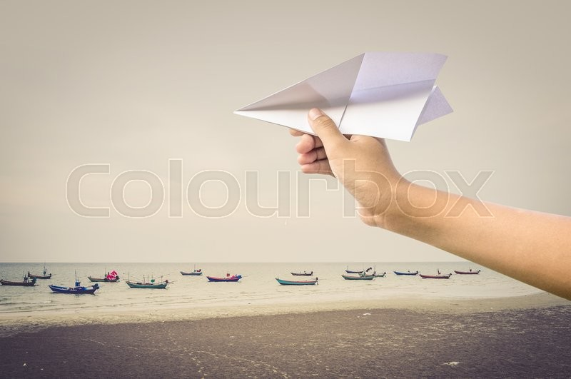 Stock image of 'plane paper in children hand over sea and boats, vintage style'